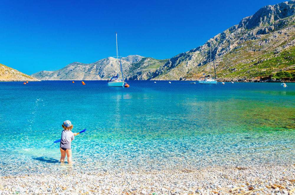 Amazing sea bay on Greek Island with a small boy at play on the seashore, Greece