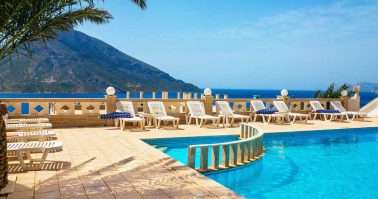 Amazing view on swimming pool area and sunbeds under palm tree with amazing view on coast and sea in background in sunny summer day, Greece