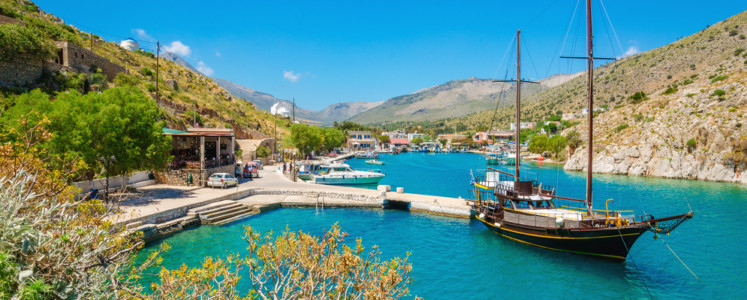 Wooden yacht standing in cosy port on Greek island with clear blue water, Greece