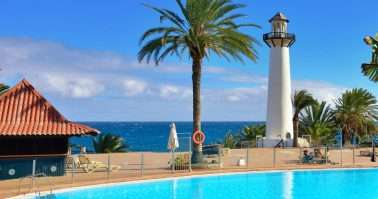 Scenic view of the lighthouse and swimming pool inside of tropical resort in the Playa del Aguila. Gran Canaria is one of the most popular tourist destination all the year.