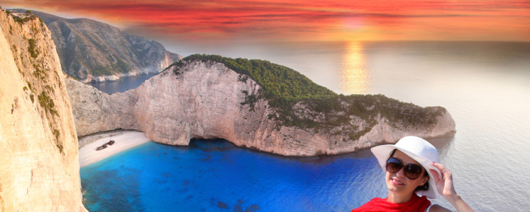 Navagio beach with woman on cliff, Zakynthos Island, Greece
